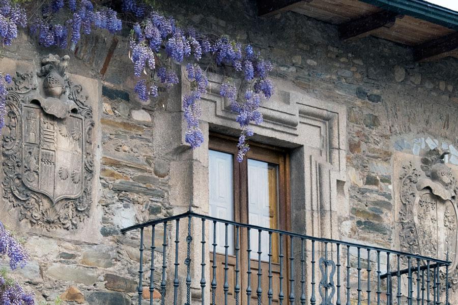 Fachada de la Casa los Escudos con glicinia florida